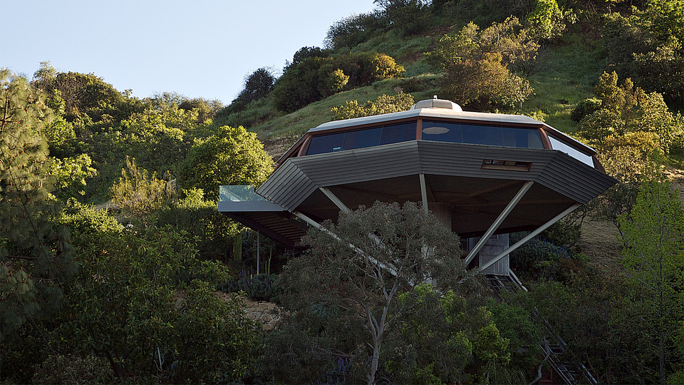 John Lautner: As with many of Lautner's buildings, the landscape of the site inspired the final design, particularly the steep, nearly 45-degree slope that was considered unbuildable. Instead of building retaining walls out from the slope to support the structure, Lautner's design hovers over the untouched landscape, supported by a 30-foot-tall reinforced concrete column. An octagon-shaped building sits on top of the column, with a roof constructed as if it were the keel and ribs of a ship. These elements create an interior that is open and free from obstructed views of the landscape and beyond.