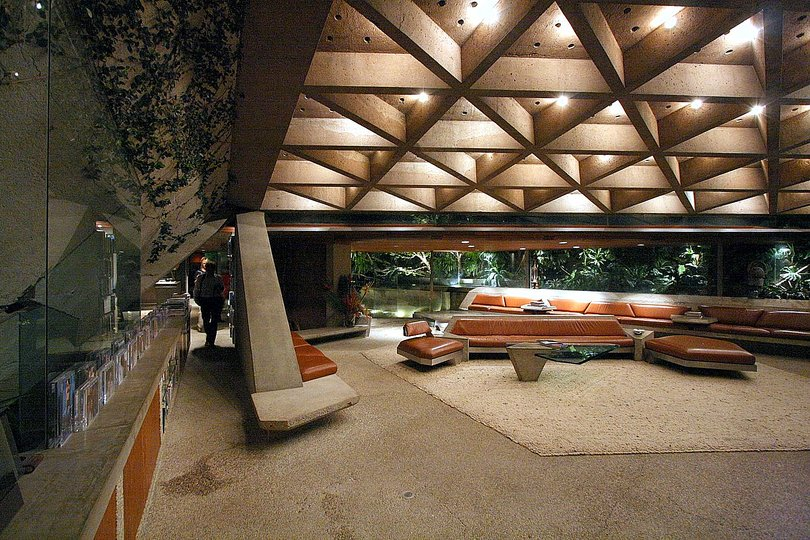 "John Lautner: Perhaps the most-seen Lautner house is the Sheats- Goldstein residence. The films ""The Big Lebowski"" (1998), ""Bandits"" (2001), and ""Charlie's Angels: Full Throttle"" (2003) are just a few of the many films that have featured the house—also a favorite of photographers. The centerpiece of the design is another concrete roof, which contains three folded, triangular surfaces. Two points touch the ground at different elevations, essentially creating a concrete sail. The interior coffered ceiling rises 18 feet overhead at the tallest point and dives down to almost six feet to allow for shade from the sun. More than 700 small drinking glasses were incorporated into the roof 's design to create tiny skylights. (Lautner considered this a way to recreate the light of a northern Michigan forest.) The natural light also allows the concrete to once again appear weightless—similar to the Garcia residence, but this time trading organic forms for purely geometric ones. The original clients, Paul and Helen Sheats, sold the house soon after it was completed in 1963. Businessman James Goldstein purchased it in 1972 and worked closely with Lautner on a series of projects to bring the design to perfection. Lautner was free to incorporate new technologies into the ongoing renovations, including concrete-and-steel furniture and a transparent sink that looks like a waterfall when in use and gives the user an uninterrupted view of the landscape."