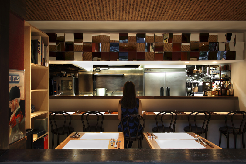 Designing a 56 sqm bistro in Tokyo: Luckily (?) the cabinet doors above the counter needed to be replaced. We covered the new ones in acrylic mirrors (12 to each door), tilted at various angles, so that people outside the restaurant would see a mosaic of the customers, tables, food, and unchanged walls and ceiling inside the store, while the customers inside would see fragments of the outside. The exterior can be seen from inside, and the interior from outside, in other words, as the area left unchanged is reflected in the renovated section, the space divided in two is simultaneously fragmented and recombined. Charming dresses, beautifully served food, crimson wine, effervescent champagne—this space transcends its partitioned structure, breaking its elements apart and then melting them together, not possessing a solid form. One could see it as the confusion resulting from an incompatibility of subject and meaning layered over one another. Architecture must of necessity deal with the concrete materials, colors, dimensions and weights of physical objects. But I would like to create something abstract with them, something rich and mellow.