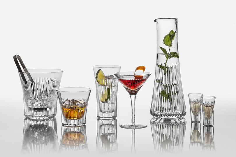 Serve Up!: Lyre Barware. A range of full lead hand-cut crystal contemporary barware that combines modern elegance with an element of classical Greece. Includes a highball glass, shot glass, martini glass and ice bucket to complement its existing water tumbler and carafe. Designer : Katy Holford for Cumbria Crystal. Stand name : CUMBRIA CRYSTAL. Show : scènes d'intérieur